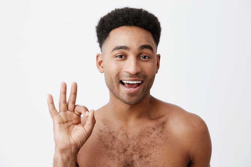 Smiling man making OK hand sign