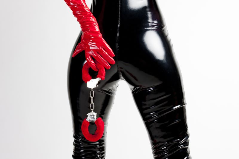 Woman's butt in latex suit with gloves and handcuffs