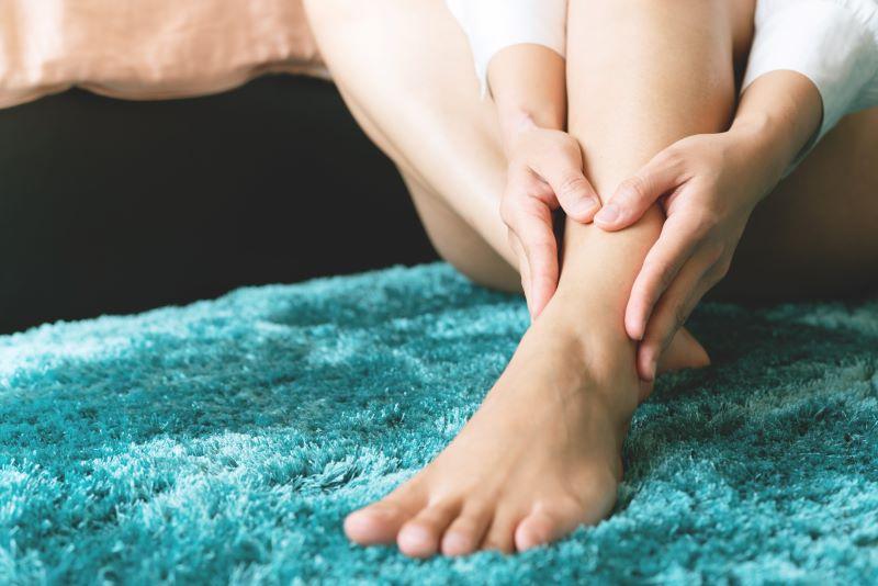 Woman giving herself foot rub