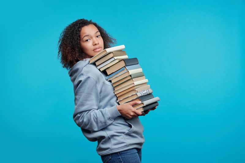 Woman holding big pile of books
