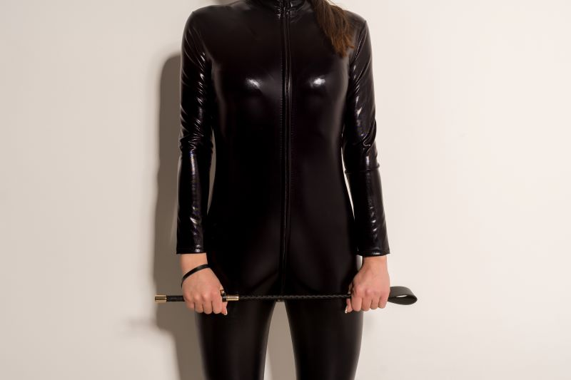 Woman holding whip in black latex bodysuit
