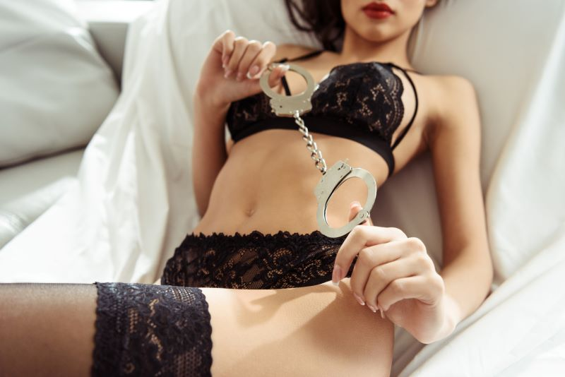 Woman in bed in lingerie holding handcuffs