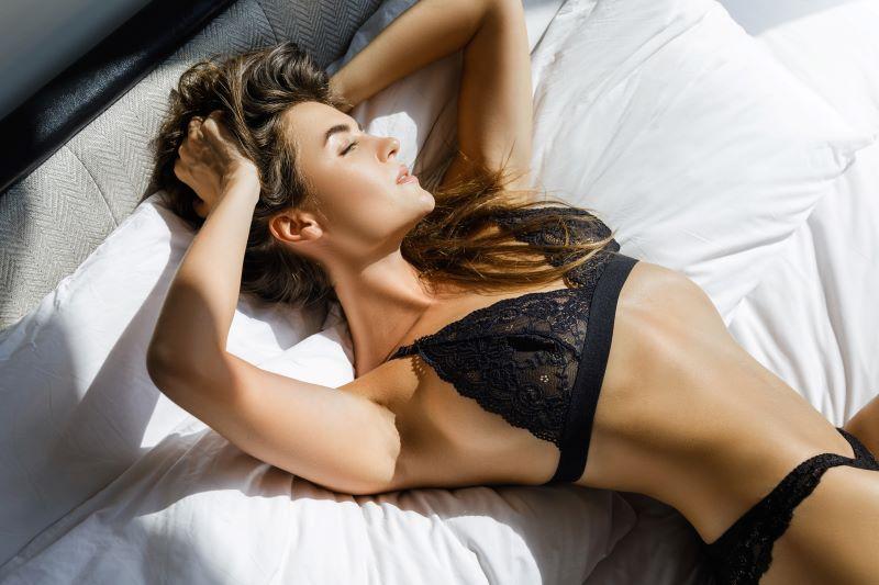 Woman posing in lingerie in bed