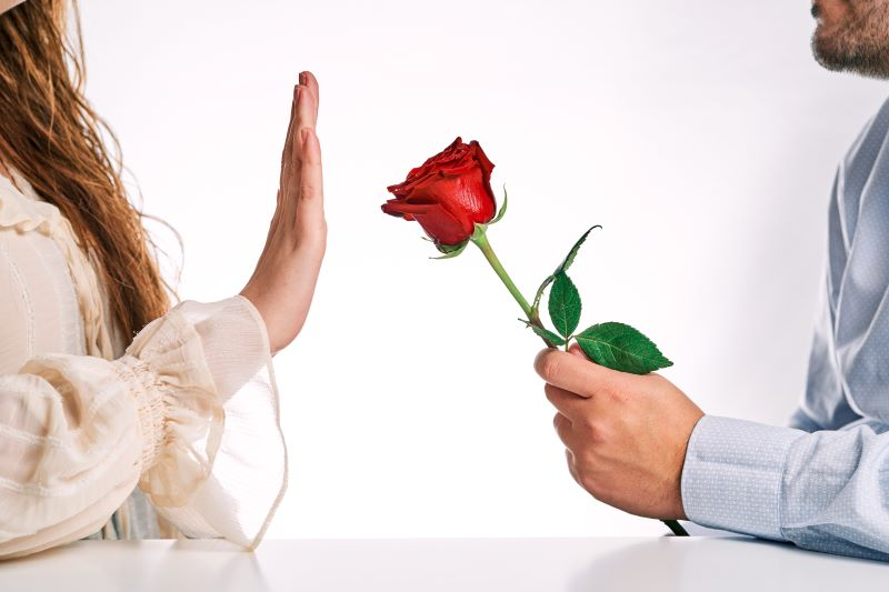 Woman rejecting red rose from her partner