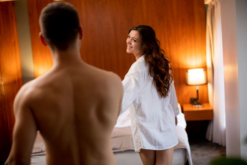 Woman seductively leading boyfriend to bed