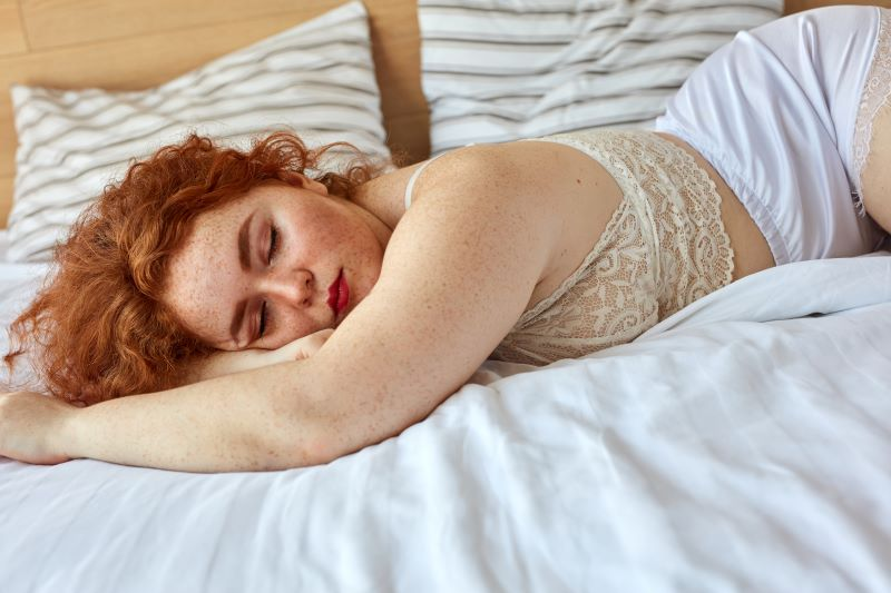 Woman sleeping in bed in lace pyjamas