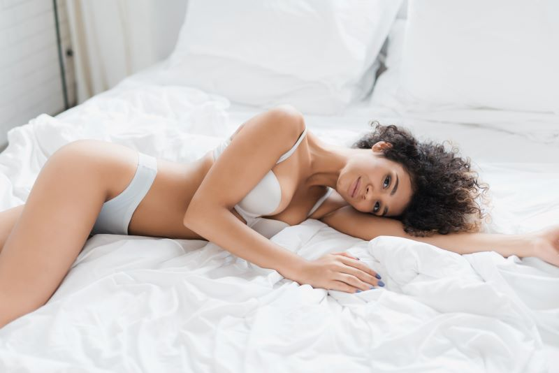 Woman smiling on bed in white lingerie