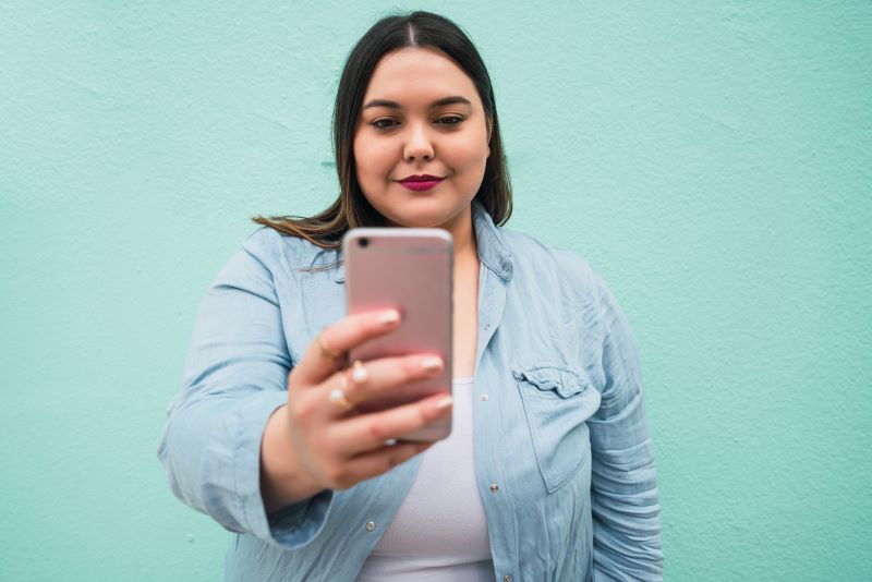 Woman taking selfie on green background