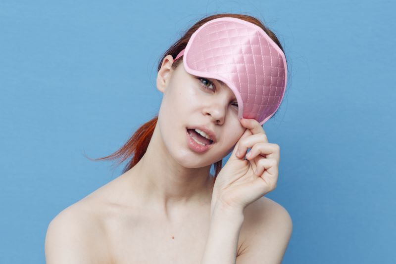 Woman holding eye mask on her head