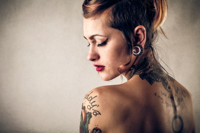Woman with tattoos and piercings posing