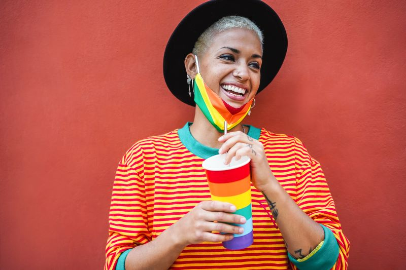 Young smiling woman holding drink with rainbow mask